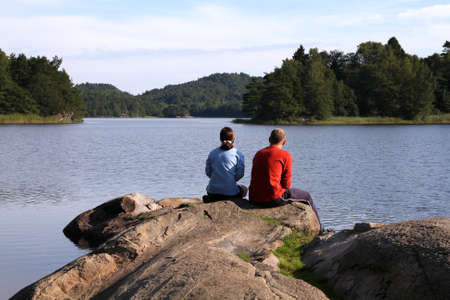 kristiansand: Romantic couple sitting on a rock by the lake Sokkevatnet in Kristiansand, Norway
