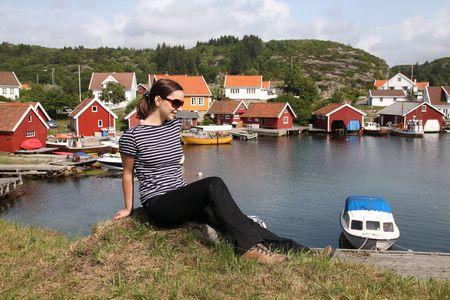 Beautiful girl traveler resting in a small harbor town on Skjernoya island, Norway. photo
