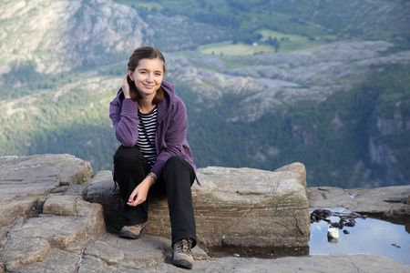 Pretty girl hiking in Norway. Resting on a rock near Preikestolen. Ryfylke district in Rogaland. photo