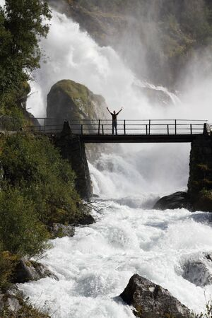 Male tourist above an extremely powerful waterfall in Briksdalen valley, Jostedalsbreen National Park in Norway. photo