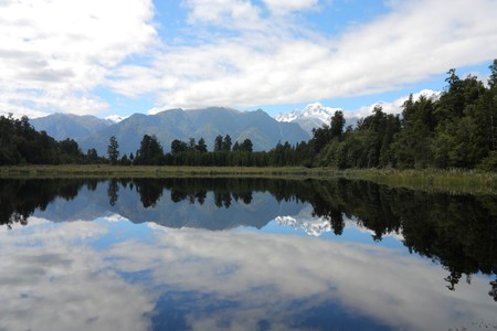 New Zealand. Lake Matheson - famous view with reflection of snowy Mount Tasman and Mount Cook. Westland district. photo