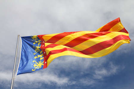 Flag of Comunidad Valenciana, region in Spain. Moving in the wind. photo