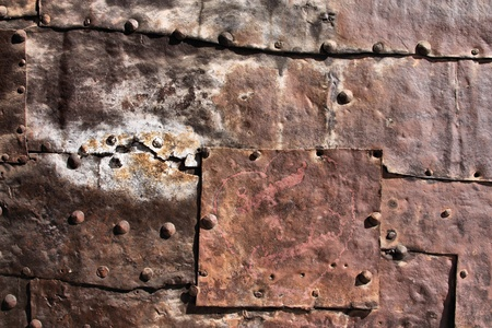 Vintage rusty iron background - metal plates with bolts. Grunge texture. photo
