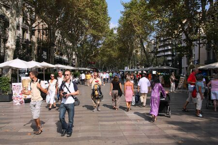 strolling: BARCELONA - SEPTEMBER 13: Tourists strolling famous Ramblas on September 13, 2009 in Barcelona. Rambla boulevard is one of the most recognized streets in the world.