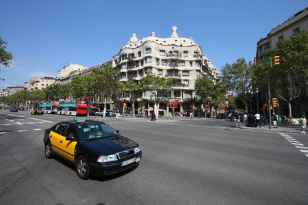 taxicabs: BARCELONA - SEPTEMBER 12: Taxi cab in front of famous Pedrera on September 12, 2009 in Barcelona. There are more than 10,000 yellow-black taxicabs in Barcelona.