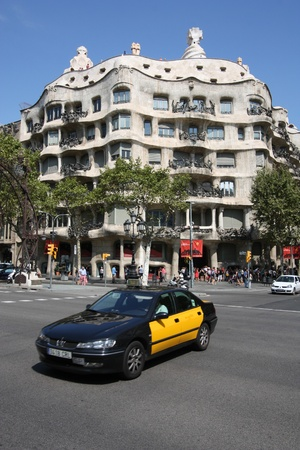 BARCELONA - SEPTEMBER 12: Taxi cab in front of famous Pedrera on September 12, 2009 in Barcelona. There are more than 10,000 yellow-black taxicabs in Barcelona.