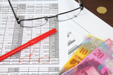 frank: Business composition. Financial analysis - income statement, red marker, glasses and Swiss frank money.
