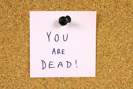 Pink sticky note pinned to an office notice board. You are dead - death threat, punishable crime. photo