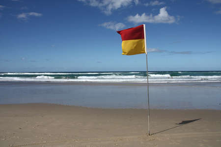 Sandy beach with safety flag in Surfers Paradise city, Gold Coast region of Queensland (Australia)