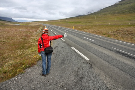 Hitchhiker in Iceland - girl traveler by the roadside. Thumbing a ride. Outdoors vacation. Stock Photo - 9262100