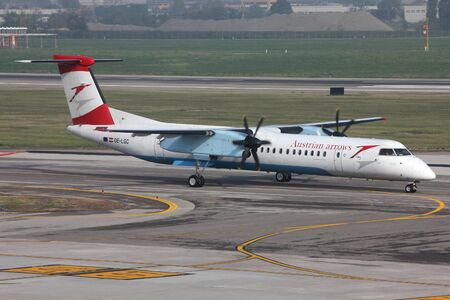BOLOGNA - OCTOBER 16: Bombardier Dash 8 turboprop of Austrian Arrows on October 16, 2010 at Bologna International Airport, Italy. With 1015 deliveries, Dash 8 is among the most successful commercial aircraft in history. Stock Photo - 9541786