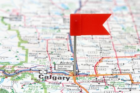 push pins: Calgary in Alberta, Canada. Red flag pin on an old map showing travel destination.