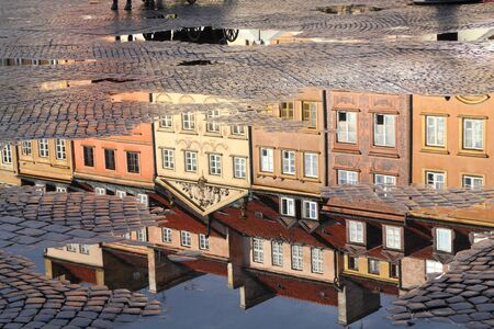 at town square: Warsaw, Poland. Old Town rain puddle reflection - tenements at the main square.  Stock Photo