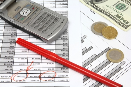 Company documents - investment analysis. Composition with US dollars, Euro coins, red pen and a mobile phone. photo