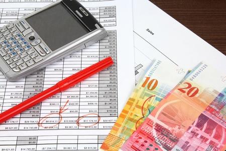 Business Objects. Analisi finanziaria - conto economico, grafici finanza, generico smart phone e valuta franco svizzero. Archivio Fotografico