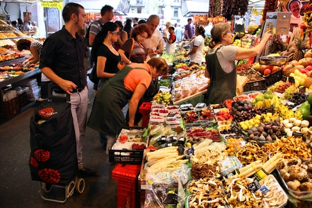 BARCELONA, SPAIN - SEPTEMBER 13: Tourists shop in famous La Boqueria market on September 13, 2009 in Barcelona, Spain. One of the oldest markets in Europe that still exist. Established 1217.