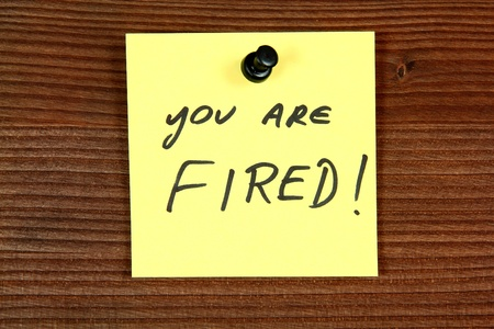 Sticky note with employment message - you are fired. Unemployment concept, job search. Bulletin board. photo