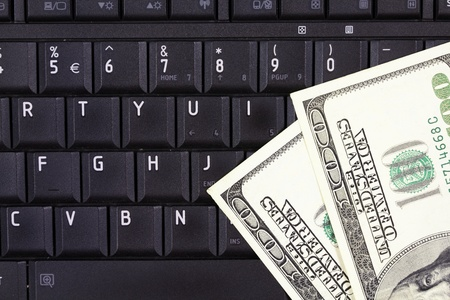Online business - notebook keyboard and US dollars Stock Photo - 11207849