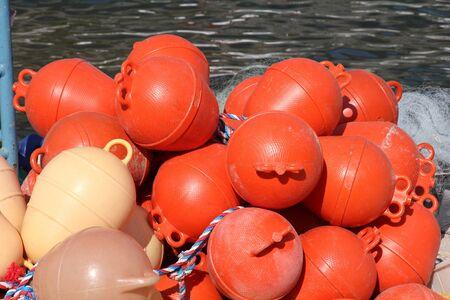 buoys: Orange plastic buoys for fishing nets. Fishing industry in Croatia.
