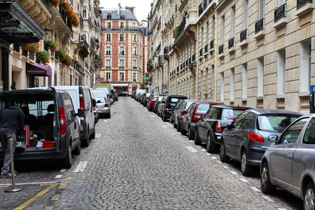 along: Paris, France - typical old city street. Cars parked along cobblestone way. Stock Photo