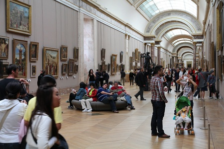PARIS - JULY 22: Visitors admire paintings on July 22, 2011 in Louvre Museum, Paris, France. With 8.5m annual visitors, Louvre is consistently the most visited museum worldwide.