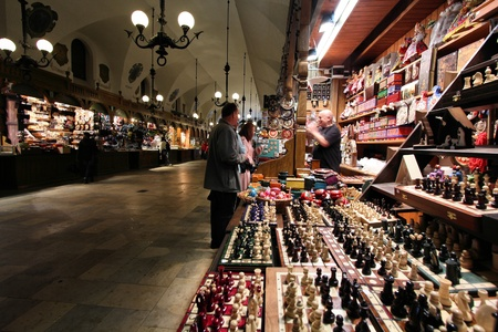 KRAKOW, POLAND - MAY 15: Tourists shop in Sukiennice Cloth Hall on May 15, 2011 in Krakow, Poland. Krakow's Old Town is a UNESCO World Heritage Site with Sukiennice being its top shopping place. Stock Photo - 11302138