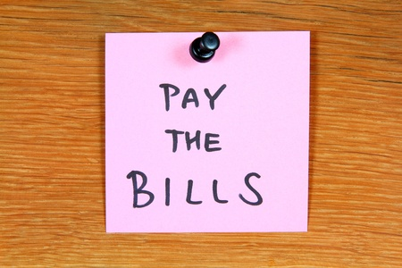 Sticky note with home expenses message: pay the bills. Bulletin board. Stock Photo - 11513308