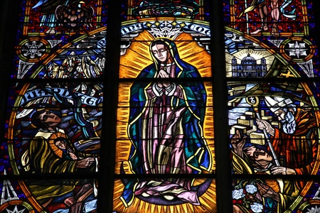 Vienna, Austria - famous Votivkirche (Votive Church) stained glass art. Virgin Mary as the Queen of Universe.