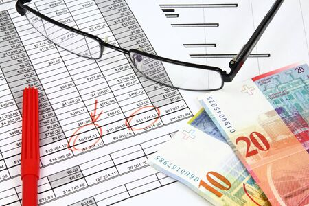 Business composition. Financial analysis - income statement, finance graphs, Swiss frank money and glasses. Stock Photo - 11574381