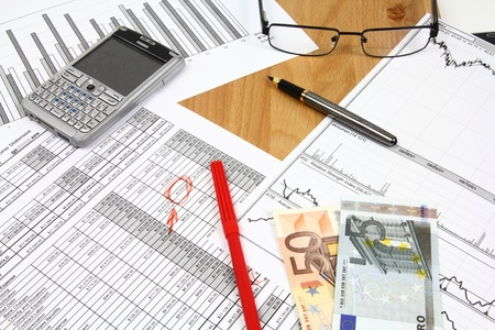 Financial documents - business related objects. Glasses, fountain pen and Euro currency money.
