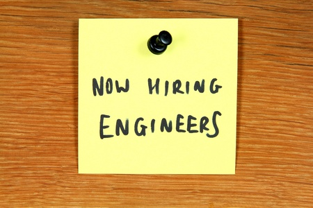 Sticky note with employment opportunity message - hiring engineers. Bulletin board. photo