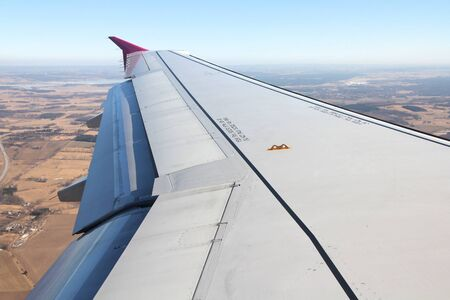 deployed: Flying over Sweden in winter. Wing view of a modern passenger aircraft. Open deployed flaps - landing approach configuration.