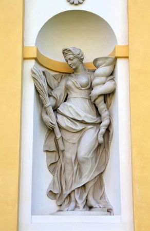 Warsaw, Poland. Famous Wilanow palace exterior - statue of Roman goddess Abundantia holding cornucopia (horn of plenty), symbol of abundance, nourishment and good harvest photo