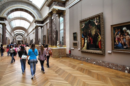 museum visit: PARIS - JULY 22: Visitors admire paintings on July 22, 2011 in Louvre Museum, Paris, France. With 8.5m annual visitors, Louvre is consistently the most visited museum worldwide.