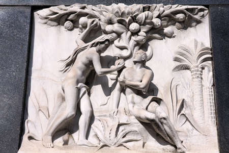Milan, Italy. Old biblical scene sculpture at the Monumental Cemetery (Cimitero Monumentale). Religious art depicting Adam and Eve picking the fruit in the garden of Eden.