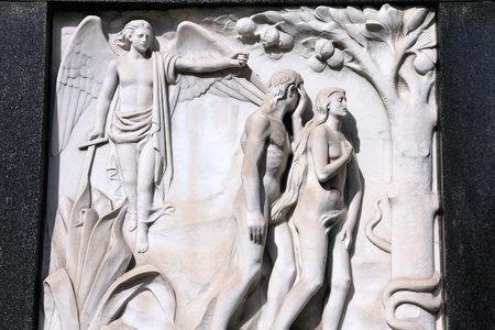 Milan, Italy. Old biblical scene sculpture at the Monumental Cemetery (Cimitero Monumentale). Religious art depicting Adam and Eve expulsion from the garden of Eden.