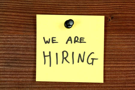 Sticky note with recruitment message - we are hiring. Employment concept, job search. Bulletin board. photo