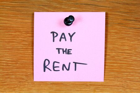 Sticky note with a message - pay the rent. Bulletin board. photo