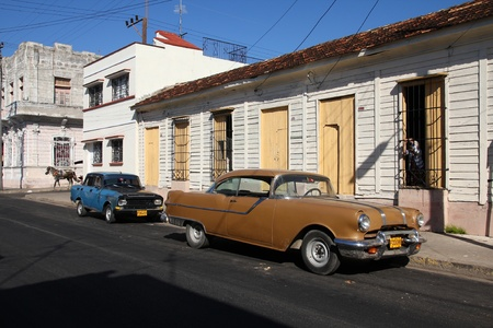 resulted: CIENFUEGOS, CUBA - FEBRUARY 3: Classic old cars in the street on February 3, 2011 in Cienfuegos, Cuba. Recent law change allows the Cubans to trade cars again. Old law resulted in very old cars in Cuba. Editorial