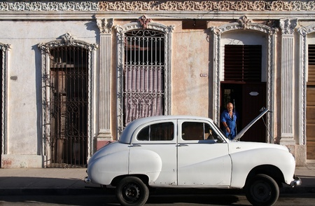 resulted: CIENFUEGOS, CUBA - FEBRUARY 3: Classic old car in the street on February 3, 2011 in Cienfuegos, Cuba. Recent law change allows the Cubans to trade cars again. Old law resulted in very old cars in Cuba.