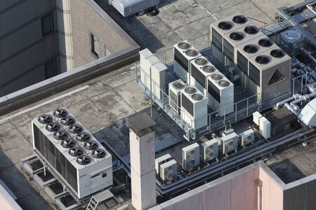 Exhaust vents of industrial air conditioning and ventilation units. Skyscraper roof top in Tokyo, Japan. Stock Photo