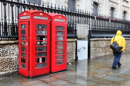 phonebox: London, United Kingdom - red telephone boxes in wet rainy weather. Wet pedestrian in a yellow rain coat.