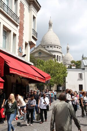 PARIS - JULY 22: Tourists visit Montmartre district on July 22, 2011 in Paris, France. Monmartre area is popular among tourists in Paris, the most visited city worldwide.