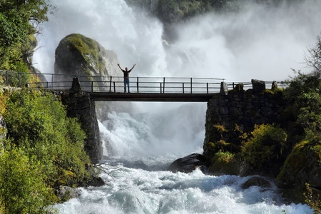 extremely: Male tourist above an extremely powerful waterfall in Briksdalen valley, Jostedalsbreen National Park in Norway.