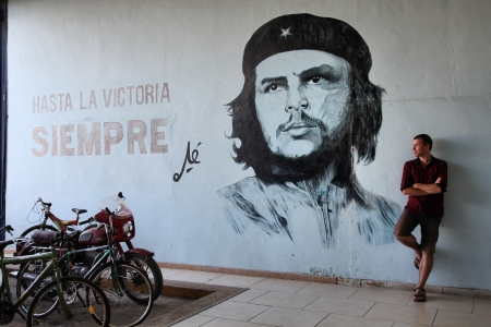 propaganda: SANTA CLARA, CUBA - FEBRUARY 22: Tourist stands next to wall mural with revolution propaganda on February 22, 2011 in Sancti Spiritus, Cuba. Revolution propaganda is promoted by national government. Editorial