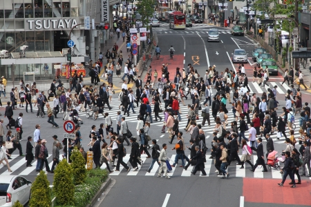 TOKYO - MAY 11: Commuters hurry on May 11, 2012 in Shibuya, Tokyo. Shibuya crossing is one of busiest places in Tokyo and is recognized thanks to being featured in multiple films. Stock Photo - 14998790