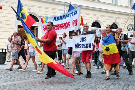 against the current: SIBIU, ROMANIA - AUGUST 23: Protesters march on August 23, 2012 in Sibiu, Romania. The protesters are against current president Traian Basescu, they compare him to corrupt communist leader Caucescu.
