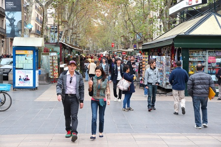 BARCELONA, SPAIN - NOVEMBER 6: Tourists walk famous Rambla street on November 6, 2012 in Barcelona, Spain. According to Mastercard, Barcelona is the 15th most visited city worldwide (7.5m in 2012). Stock Photo - 16310012