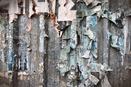 vandalism: Torn posters on old metal wall - vandalism and urban decay in Spain Stock Photo