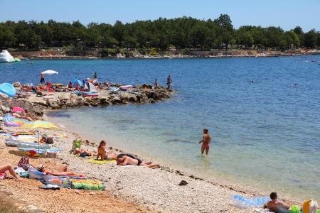 vacationers: POREC, CROATIA - JUNE 20: Vacationers enjoy the beach on June 20, 2011 in Porec, Croatia. In 2011 11.2 million tourists visited Croatia, most of them in summer. Editorial